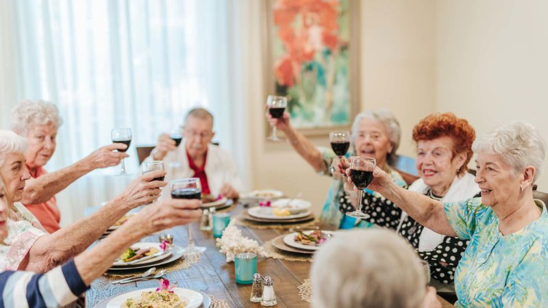 Group of seniors dining together in private dining room toasting their glasses